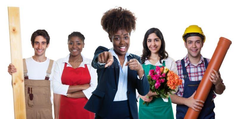Señalar a la empresaria afroamericana con el grupo de otros aprendices foto de archivo