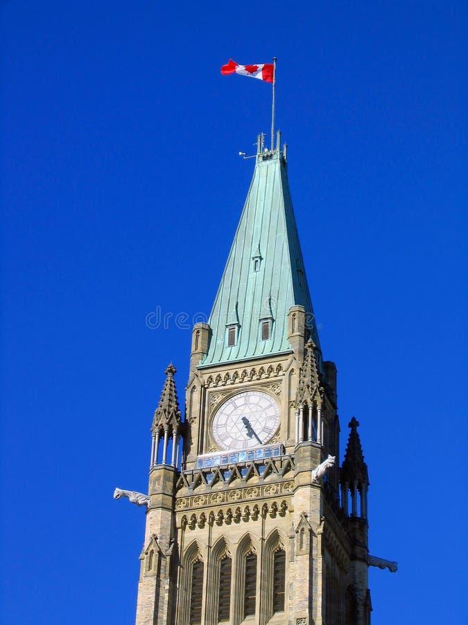 Señale el vuelo por medio de una bandera en torre de reloj del edificio canadiense del parlamento en Ottawa, Ontario fotos de archivo