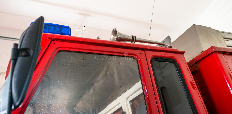 Señales de peligro azules y una sirena colocada en el tejado de un coche de bomberos imágenes de archivo libres de regalías