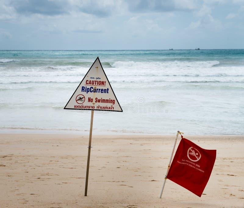 Señales de peligro sobre corriente de rasgón en una playa imagenes de archivo