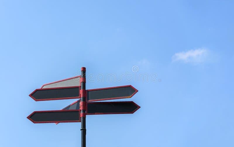 Señales de tráfico direccionales en blanco contra el cielo azul Flechas rojas negras en el poste indicador imagenes de archivo