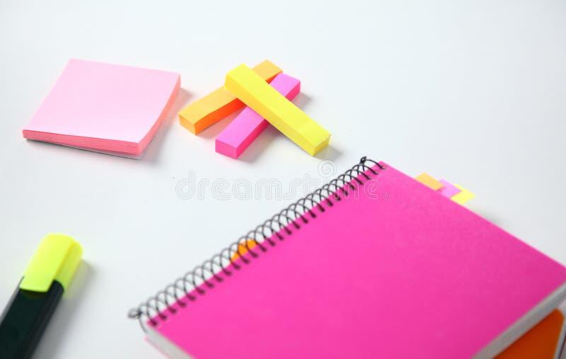 Señales pegajosas coloridas para el cuaderno, las grapadoras y la pluma en el fondo blanco Foco selectivo imagenes de archivo