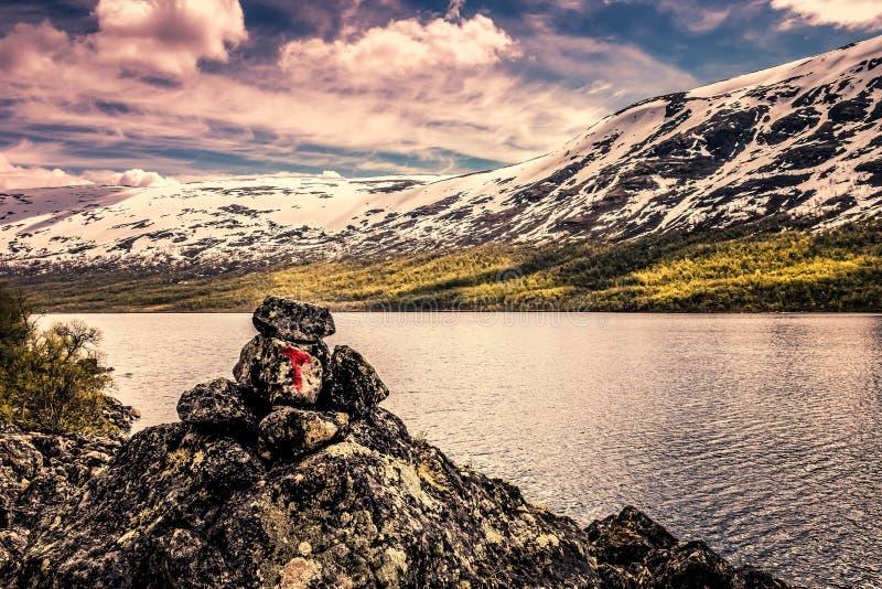 Señalice para el rastro delante de un lago y las montañas nevosas en Noruega imagen de archivo