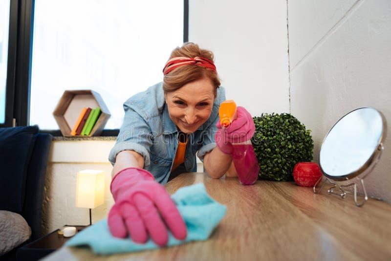 Señora adulta contenta de emisión que se ocupa de la limpieza en su apartamento fotografía de archivo libre de regalías