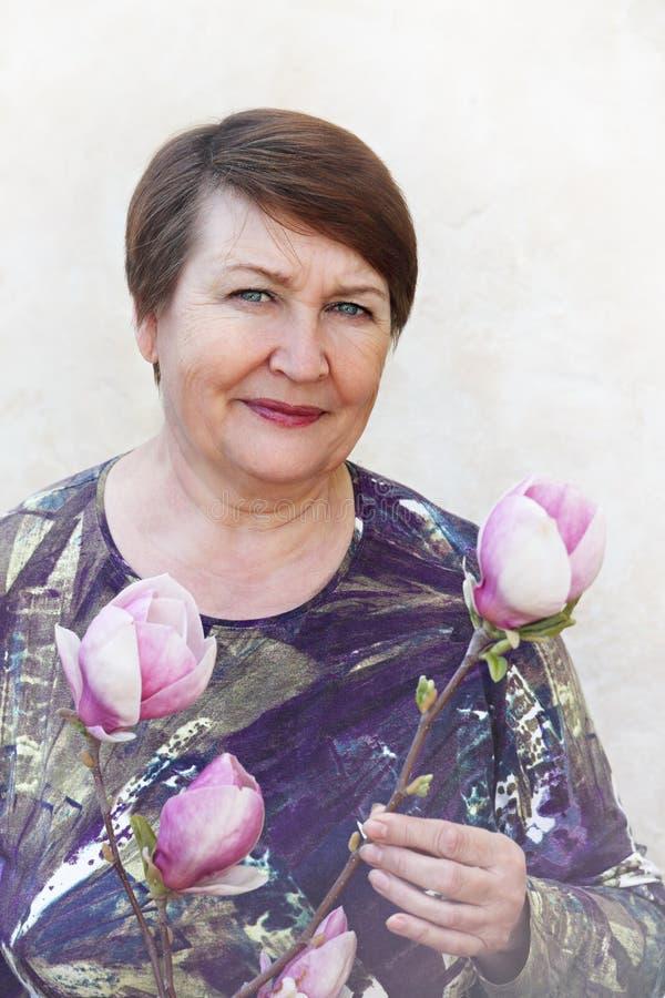 Señora adulta que lleva a cabo una rama de la magnolia foto de archivo