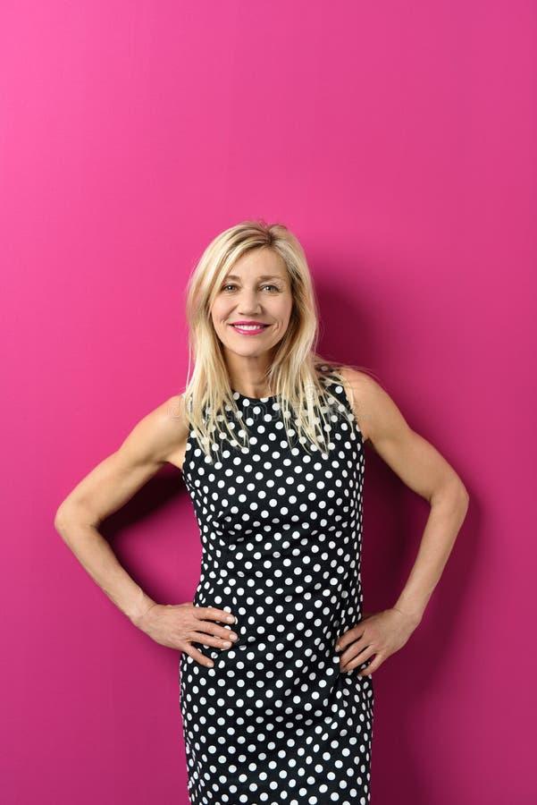 Señora adulta sonriente en vestido punteado contra rosa foto de archivo