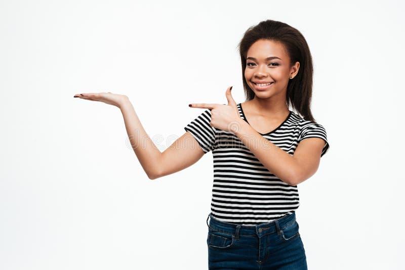 Señora africana joven feliz que lleva a cabo el copyspace disponible mientras que señala fotografía de archivo libre de regalías