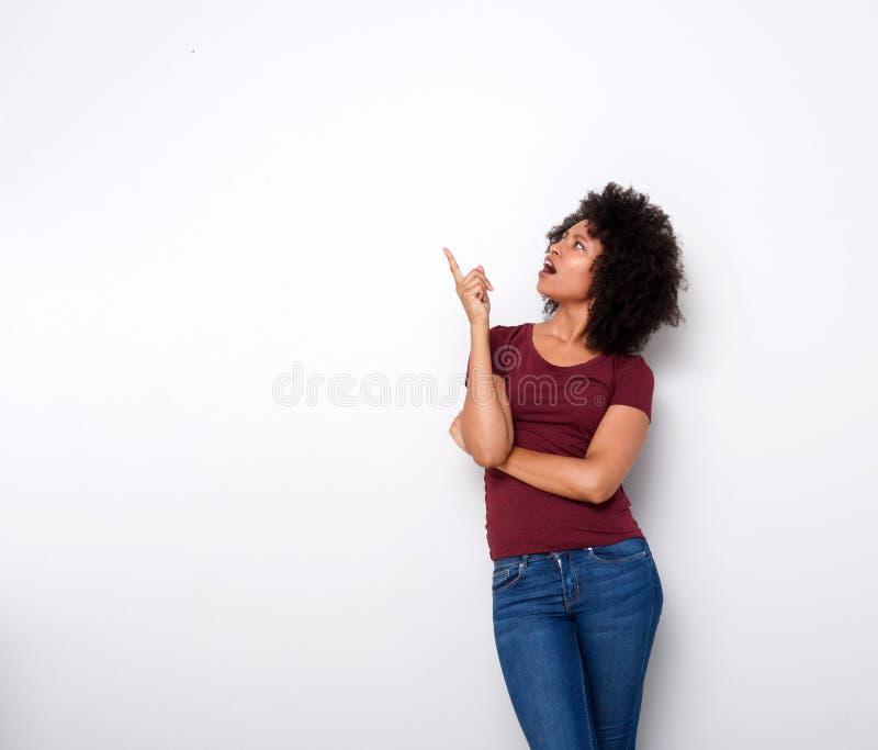 Señora africana joven sorprendida que mira para arriba y que señala en el fondo blanco imagen de archivo