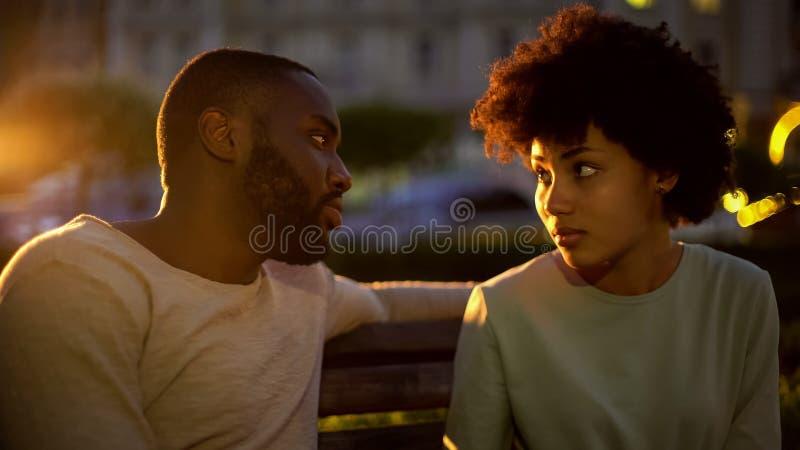 Señora afroamericana que mira al novio con la esperanza, malentendido, conflicto imagenes de archivo