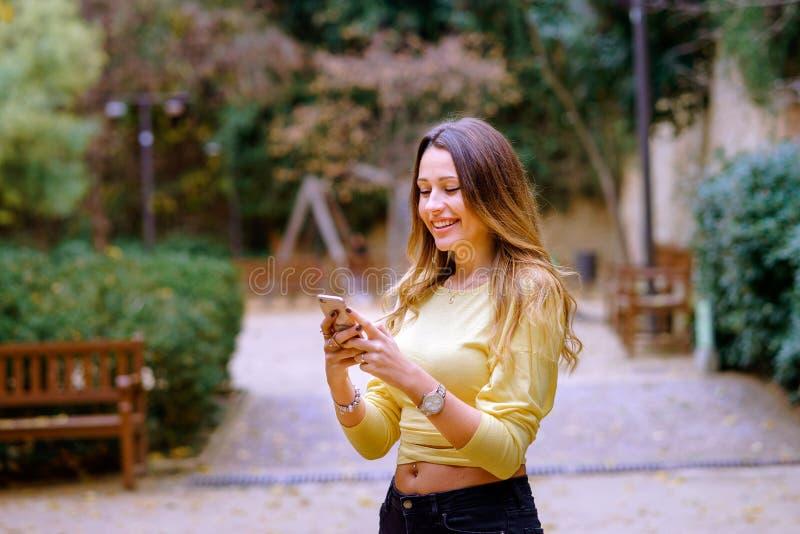 Señora alegre usando smartphone en parque imágenes de archivo libres de regalías