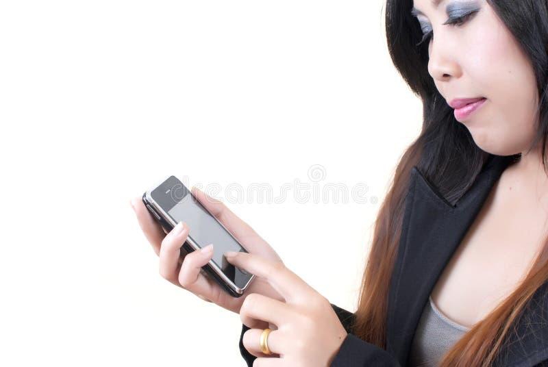 Señora asiática del asunto que empuja el teléfono móvil para el commu foto de archivo libre de regalías