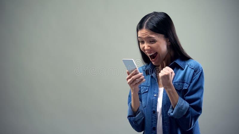 Señora asiática que sostiene smartphone, sinceramente disfrutando, tarifas favorables para las llamadas foto de archivo libre de regalías