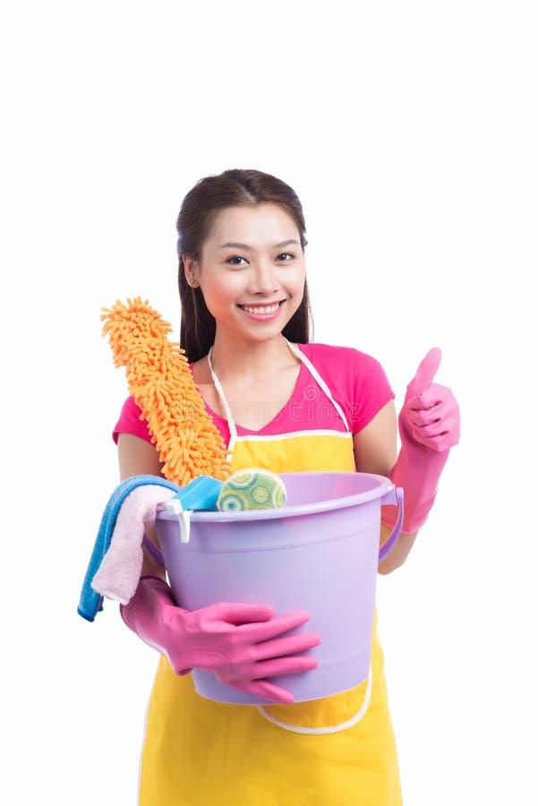 Señora asiática sonriente de la limpieza joven con el showin de goma rosado de los guantes fotografía de archivo libre de regalías