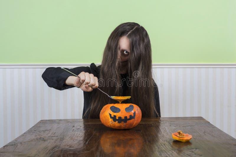 Señora asustadiza que come la sopa de la calabaza fotografía de archivo