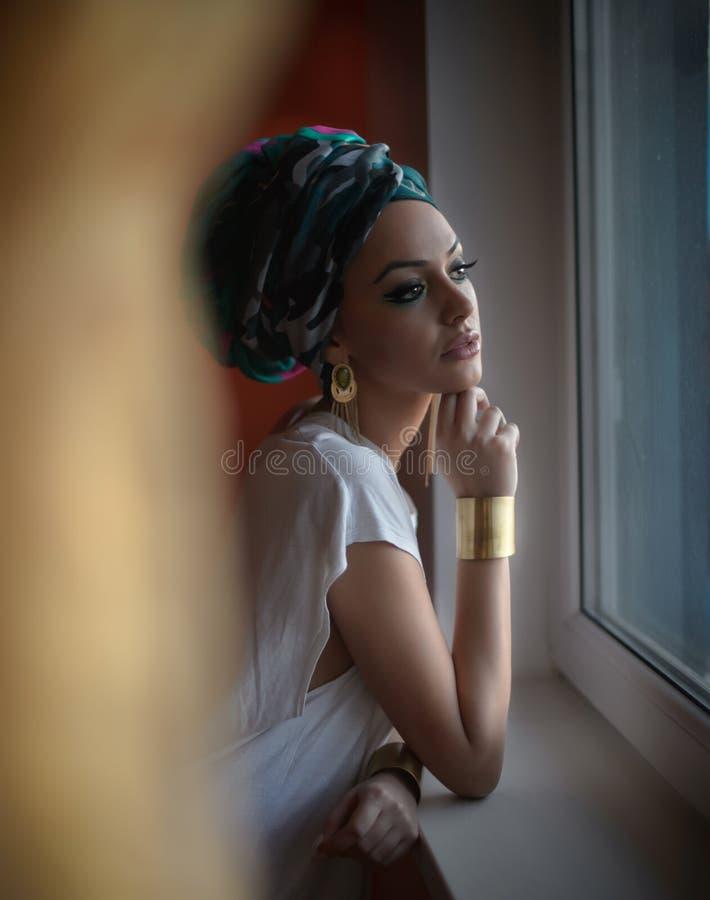 Señora atractiva atractiva en la blusa blanca que presenta en el marco de ventana que mira afuera Retrato de la mujer joven sensu fotos de archivo libres de regalías