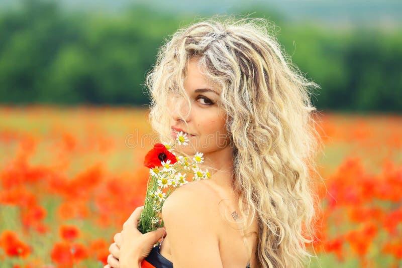 Señora atractiva bonita con el pelo rizado rubio que cayó en su cara, en un campo rojo hermoso de la amapola, las vueltas a la cá fotografía de archivo libre de regalías