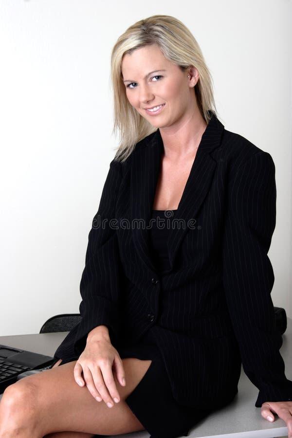 Señora atractiva de la oficina que se sienta en su escritorio fotos de archivo