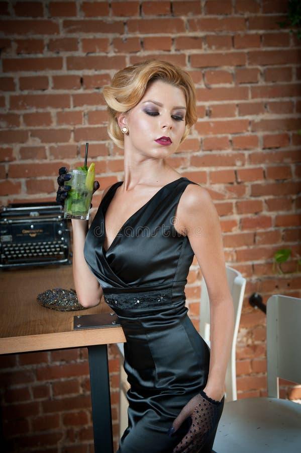Señora atractiva de moda con poco vestido y guantes negros que se colocan cerca de una tabla en el restaurante que sostiene un vi foto de archivo libre de regalías