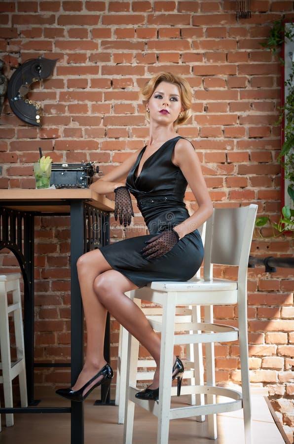 Señora atractiva de moda con poco vestido y guantes negros que se sientan en silla en el restaurante que tiene una bebida en la t imagen de archivo libre de regalías