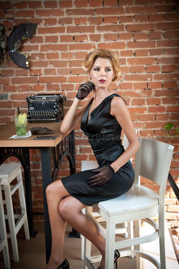 Señora atractiva de moda con poco vestido y guantes negros que se sientan en silla en el restaurante que tiene una bebida en la t imagen de archivo