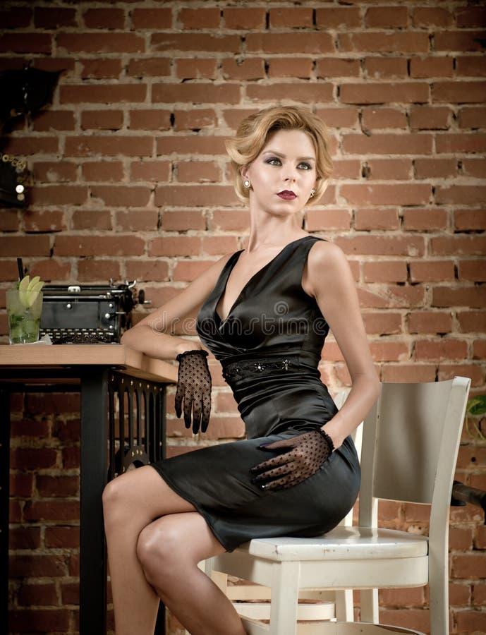 Señora atractiva de moda con poco vestido y guantes negros que se sientan en silla en el restaurante que tiene una bebida en la t foto de archivo libre de regalías