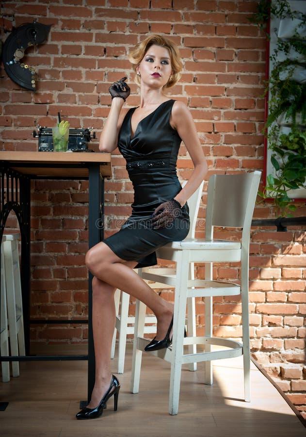 Señora atractiva de moda con poco vestido y guantes negros que se sientan en silla en el restaurante que tiene una bebida en la t fotografía de archivo libre de regalías