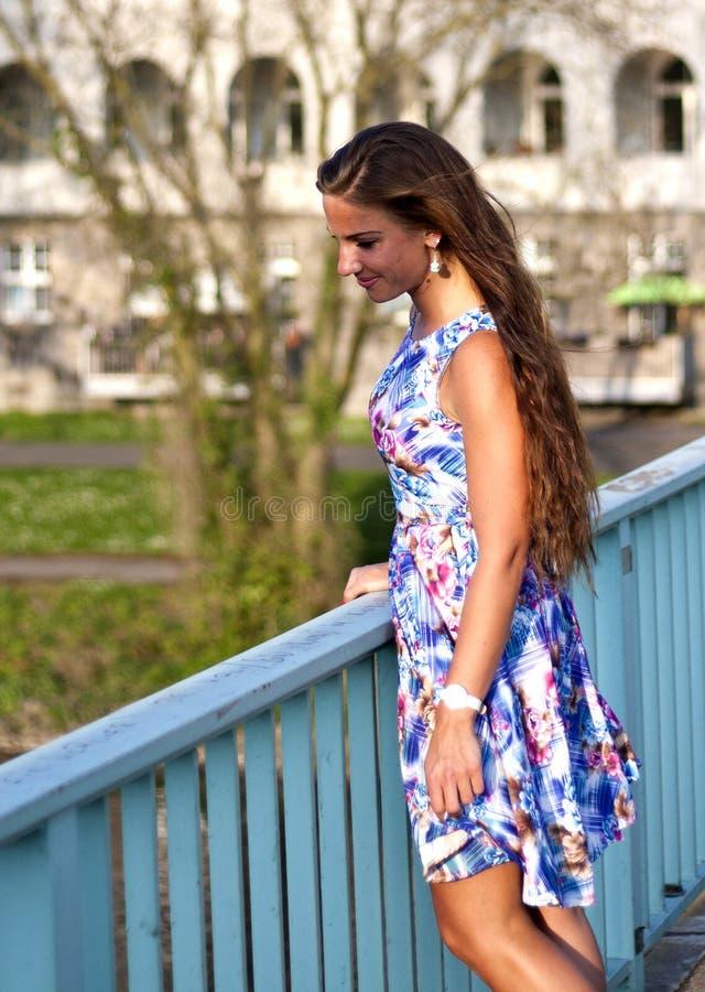 Señora atractiva del brunnete que se coloca en el puente fotografía de archivo libre de regalías