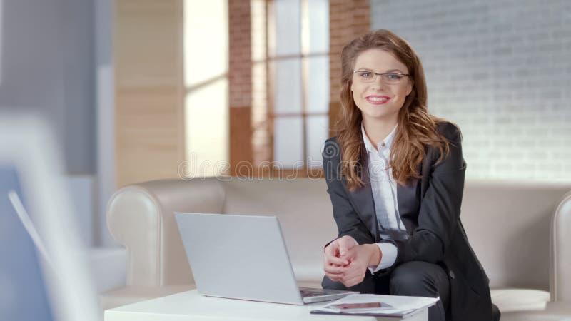 Señora atractiva en vidrios que sonríe en el empleado de la cámara, elegante y responsable fotografía de archivo libre de regalías