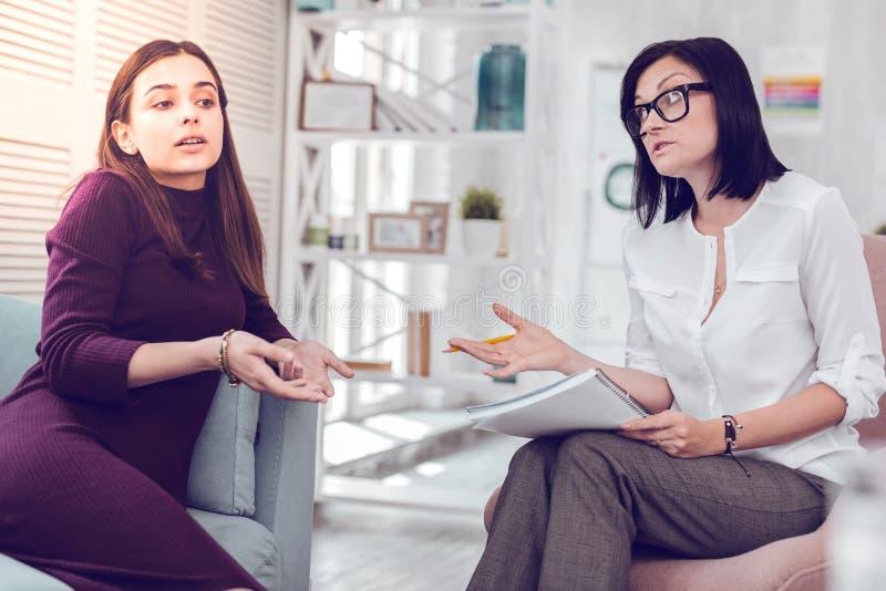 Señora atractiva hermosa del joven-adulto que discute problemas de la relación con un psicólogo foto de archivo libre de regalías