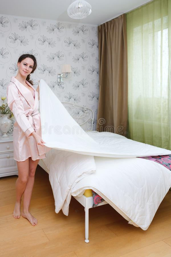 Señora atractiva hermosa en el traje blanco coralino de la puntilla que plantea sostenerse combinado en la cama en el dormitorio  foto de archivo