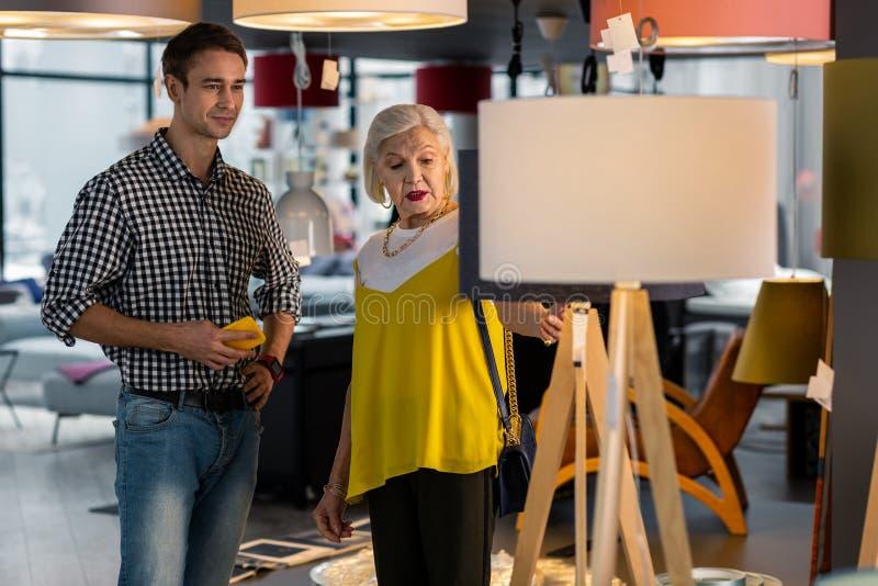 Señora atractiva mayor que elige la lámpara de pie con el hombre hermoso joven fotografía de archivo