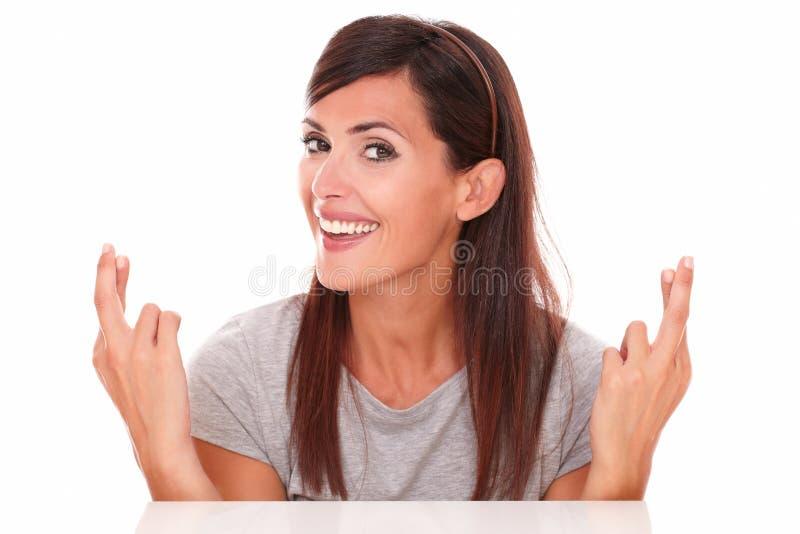 Señora atractiva que cruza sus fingeres mientras que sonríe foto de archivo libre de regalías