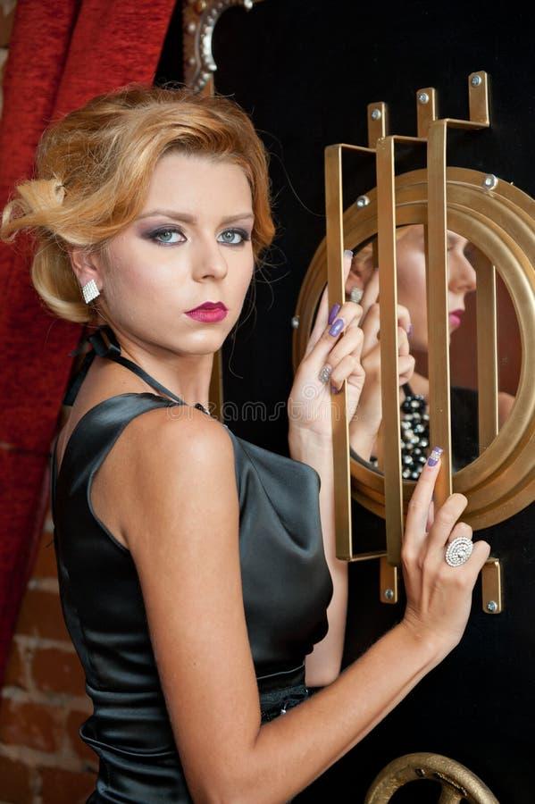 Señora atractiva sensual de moda con el vestido negro que se coloca cerca de una caja fuerte en una escena del vintage Mujer del  imagenes de archivo