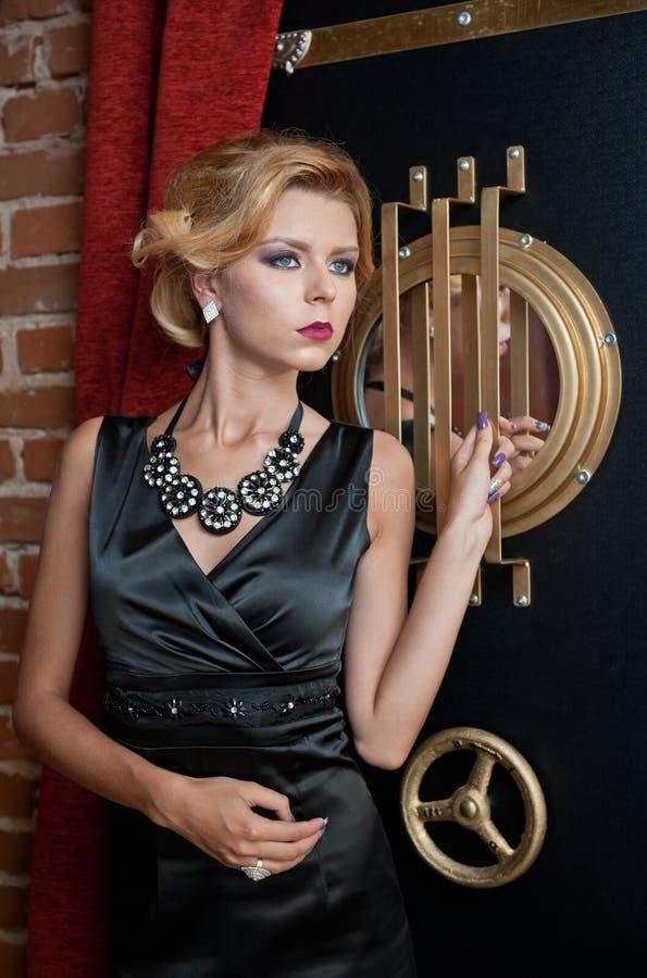 Señora atractiva sensual de moda con el vestido negro que se coloca cerca de una caja fuerte en una escena del vintage Mujer del  fotografía de archivo