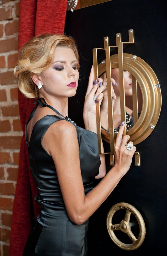 Señora atractiva sensual de moda con el vestido negro que se coloca cerca de una caja fuerte en una escena del vintage Mujer del  fotografía de archivo libre de regalías