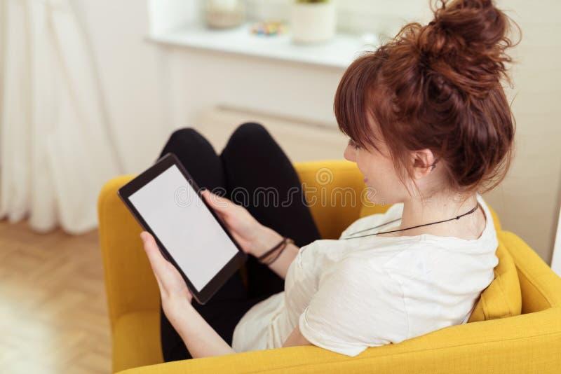 Señora bastante joven en una silla que sostiene su tableta foto de archivo