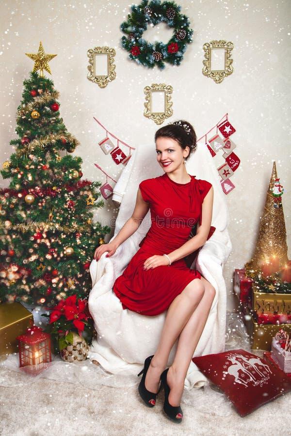 Señora bastante joven en vestido rojo entre la decoración de la Navidad fotos de archivo