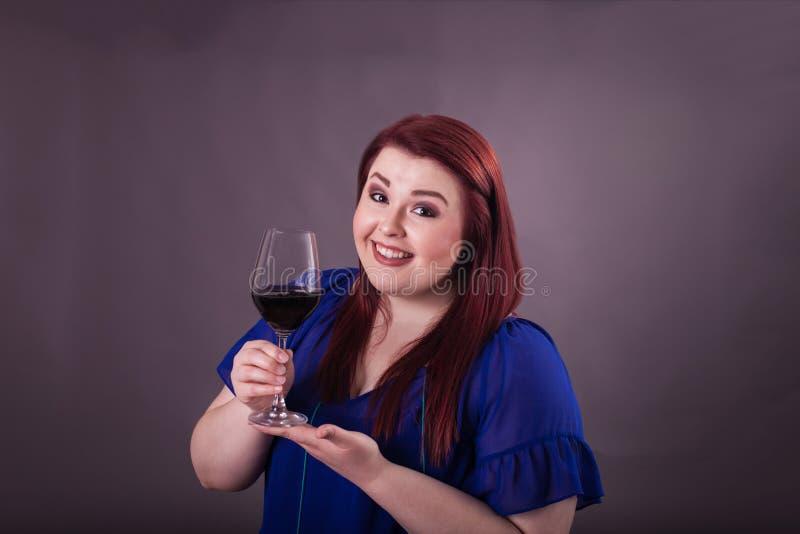 Señora bastante joven que presenta gozando de un vidrio de vino rojo fotografía de archivo