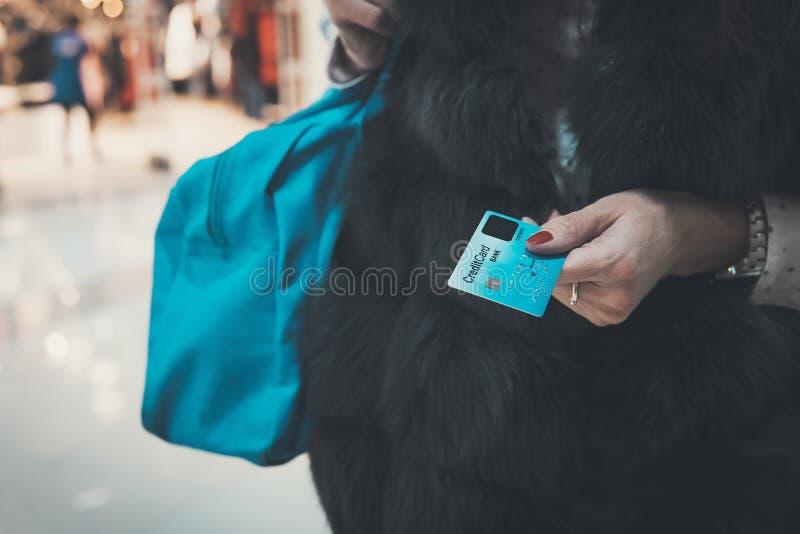 Señora bien vestida en la piel que sostiene la tarjeta y el bolso de crédito en el fondo borroso de la alameda Mujer que paga en  imagen de archivo