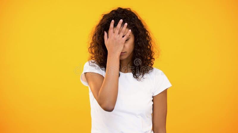 Señora biracial del descontento que gesticula la palma de la cara en cámara contra fondo amarillo imagenes de archivo