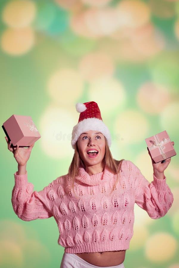 Señora bonita en el sombrero de Papá Noel que sostiene el regalo rosado dos imágenes de archivo libres de regalías