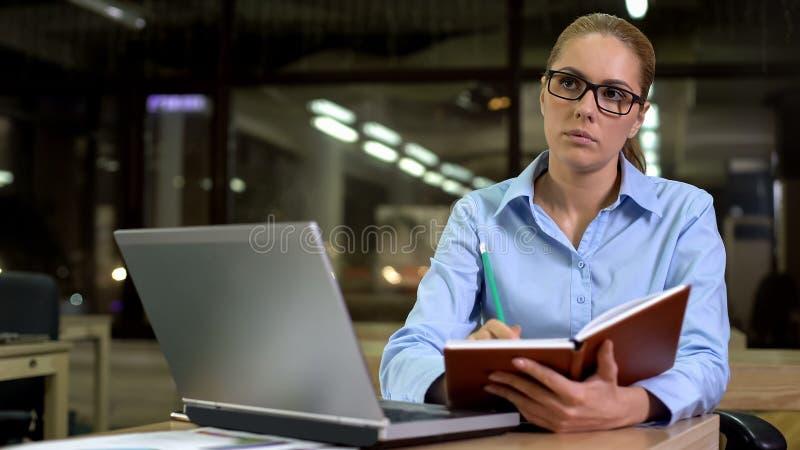 Señora bonita que piensa en ideas de lanzamiento, reunión de planificación, cuaderno del negocio imagenes de archivo