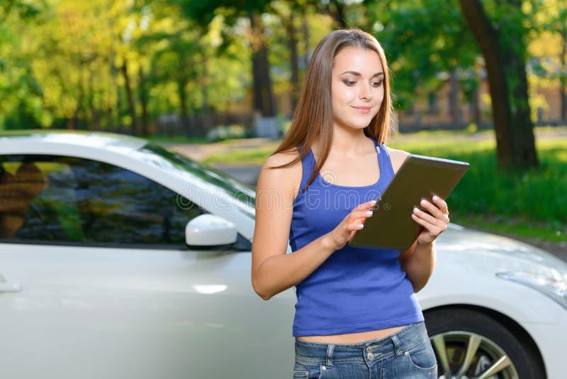 Señora bonita que se coloca con la tableta cerca del coche imagen de archivo libre de regalías