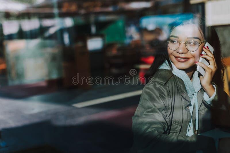 Señora cabelluda oscura que sonríe mientras que teniendo charla agradable del teléfono foto de archivo