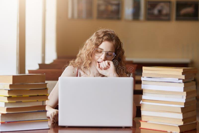 Señora cansada agotada que se sienta en el escritorio en la biblioteca, cubriendo su boca con el puño mientras que bosteza, traba imagen de archivo