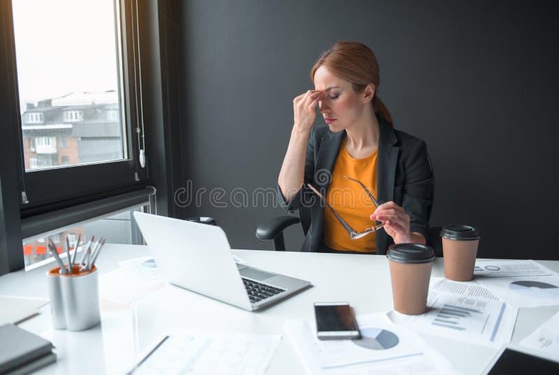 Señora cansada que tiene trabajo con el ordenador portátil fotografía de archivo