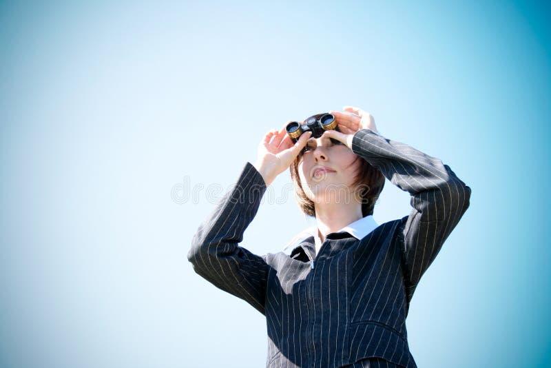 Señora caucásica joven del asunto con los prismáticos imagenes de archivo