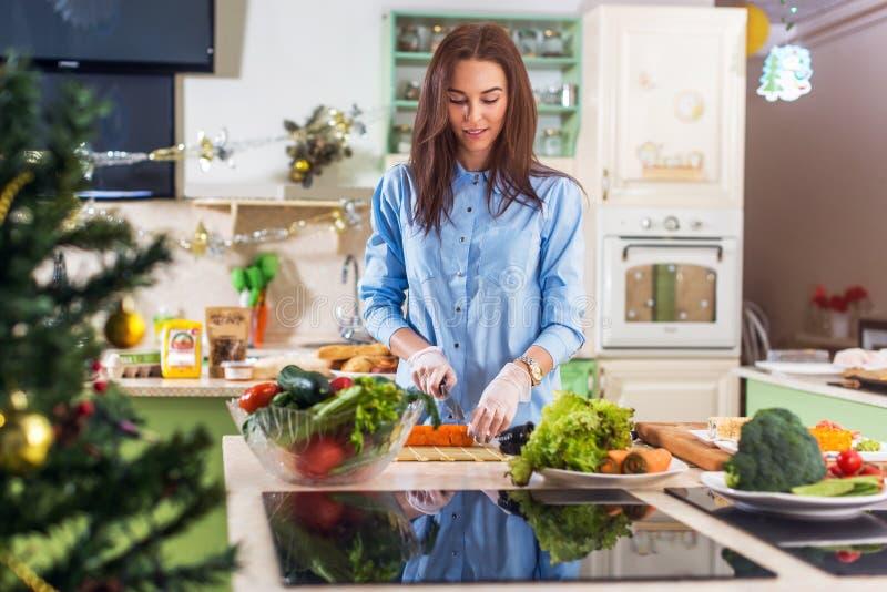 Señora caucásica joven que cocina la comida del Año Nuevo o de la Navidad en cocina adornada en casa foto de archivo libre de regalías
