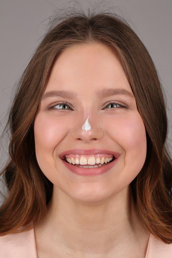 Señora con crema en su nariz Cierre para arriba Fondo gris imágenes de archivo libres de regalías