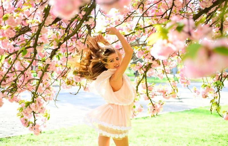 Señora con la sonrisa encantadora que presenta debajo de cereza japonesa Muchacha rubia en vestido rosado precioso que disfruta d imagen de archivo libre de regalías
